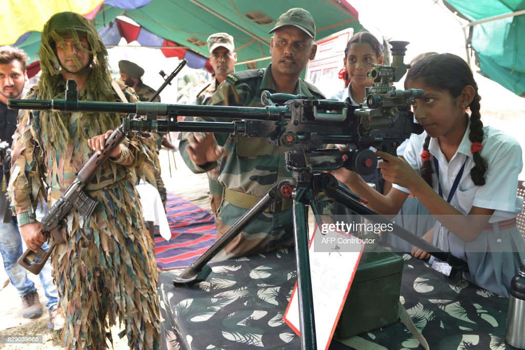 Indian Army personnel explain the use of a MMG 762 MM gun to school girls during an Indian Army exhibition at Panther Stadium in Amritsar on August...