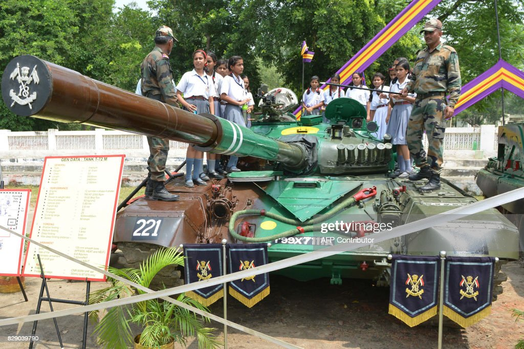 Indian Army personnel explain the use of a T72 M tank to school girls during an Indian Army exhibition at Panther Stadium in Amritsar on August 10...