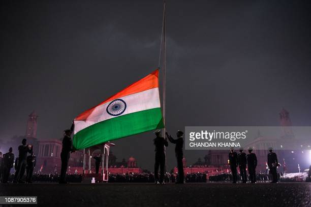 TOPSHOT Indian Army personnel lower India's national flag during the rehearsal at the Beating Beating Retreat Ceremony at Vijay Chowk in New Delhi on...