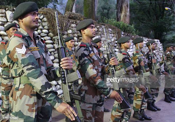 Indian army personnel stand to attention during a wreath laying ceremony for the Indian army soldiers, who were killed during an ambush, at Brigade...