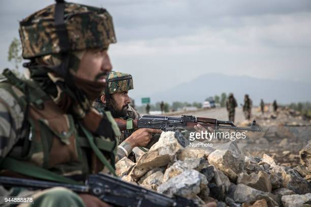 Indian army personnel take position near the gunfight site Wednesday April 11 in Khudwani village about 60 kilometres south of Srinagar...