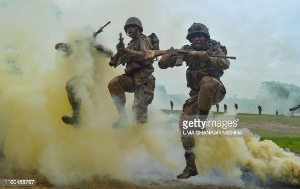 TOPSHOT Indian Army recruits shout and jump next to colourful smoke during a training demonstration at the Jak Rifles regimental centre in Jabalpur...