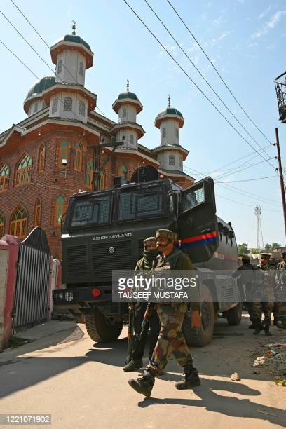 Indian army soldiers are seen in front of a mosque at the site of a gunbattle at Meej Pampore area of Pulwama district, south of Srinagar on June 19,...
