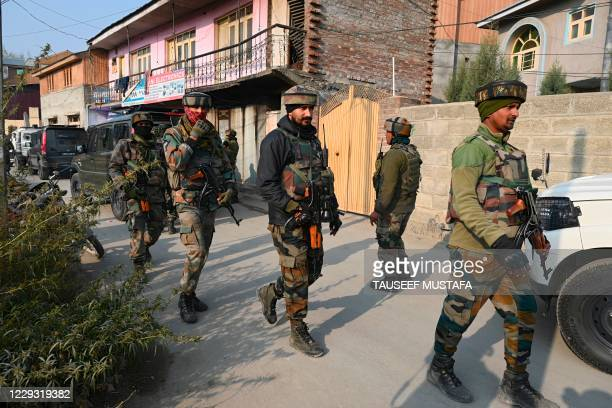 Indian army soldiers are seen near the site of a gunbattle between suspected militants and government security forces at Moachwah in Chadoora area of...