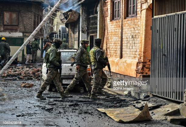 Indian army soldiers are seen walking towards house where militants were believed to be hiding from during during the clashes Clashes broke out...