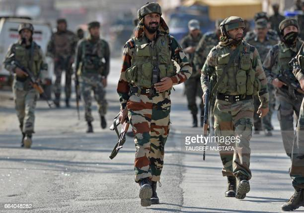Indian army soldiers arrive at the scene of an attack on a Indian Central Reserve Police Force convoy at Panthachowk on the outskirts of Srinagar on...