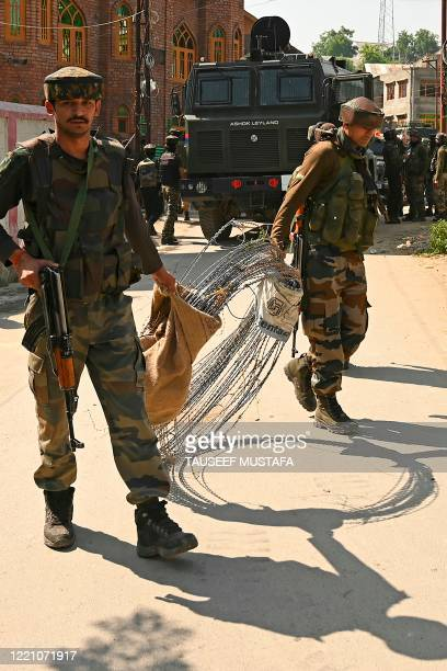 Indian army soldiers carry a barbed fence wire as they prepare to leave near a mosque at the site of a gunbattle at Meej Pampore area of Pulwama...