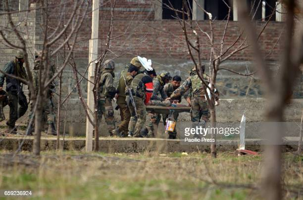 Indian army soldiers carry their injured comrade in central Kashmirs Chadoora some 20 kilometers from Srinagar the summer capital of Indian...