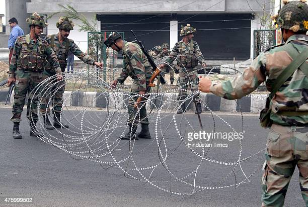 Indian Army soldiers closes the road with concertina razor wire during a curfew on June 5 2015 in Jammu India Indefinite Curfew was by the...