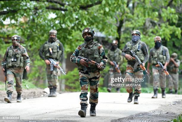 Indian army soldiers conduct a patrol during an operation against suspected rebels in Turkwangam Lassipora in Shopian south of Srinagar on May 4 2017...