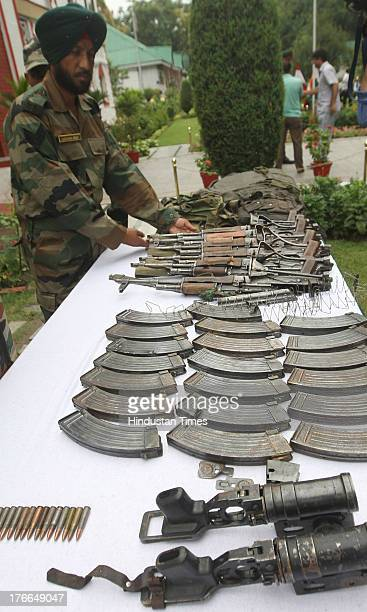 Indian Army soldiers display arms and ammunition seized during operation against militants along Line of Control and other parts in Kashmir during...