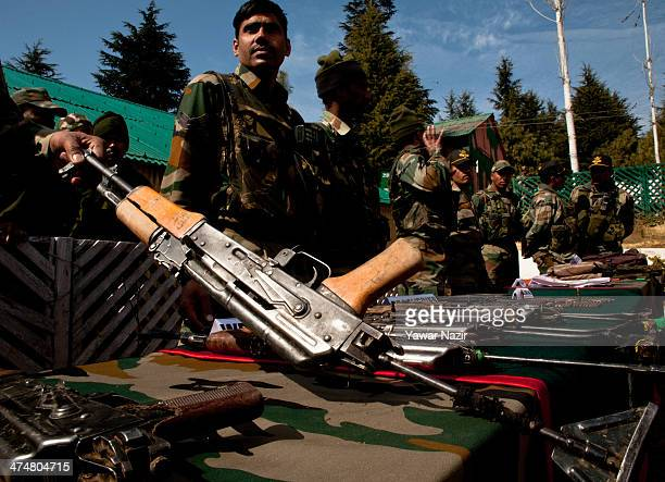 Indian army soldiers display seized arms and ammunition recovered from a group of suspected militants it says were killed on February 25 2014 in...