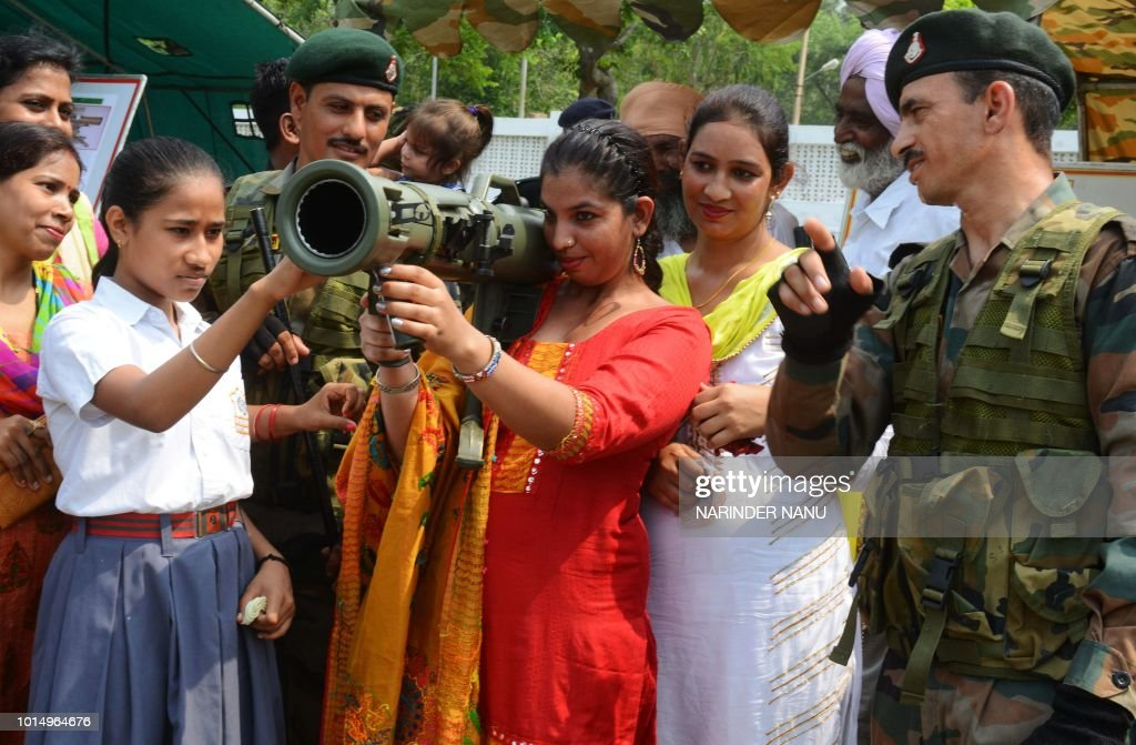 Indian army soldiers explain the use of an 84MM rocket launcher to visitors during an Indian Army exhibition at Panther Stadium in Amritsar on August.