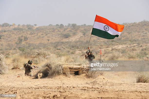 Indian army soldiers from 5 Assam Battalion hold the Indian national flag after capturing enemy bunkers during the Indian Army Exercise Sudarshan...