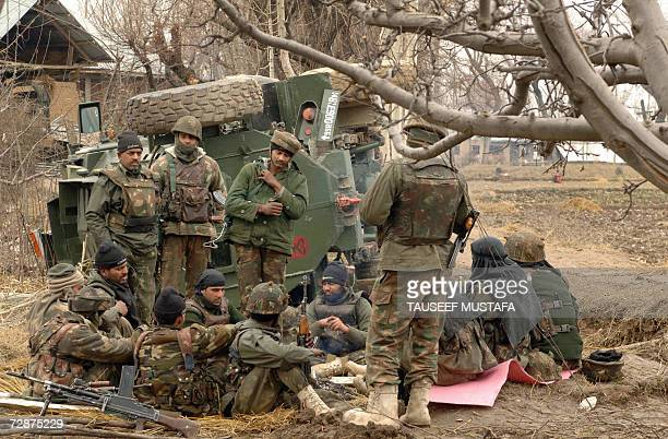 Indian Army soldiers keep themselves warm next to a fire near an overturned armoured vehicle during a gun battle with Muslim rebels in Tilgam village...