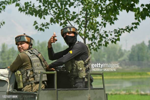 Indian army soldiers leave in a vehicle near a mosque at the site of a gunbattle at Meej Pampore area of Pulwama district, south of Srinagar on June...