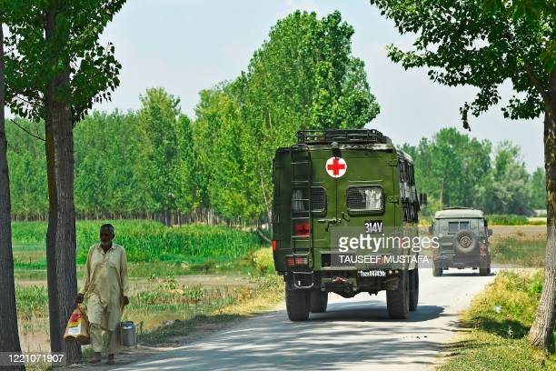 Indian army soldiers leave in their vehicles near a mosque at the site of a gunbattle at Meej Pampore area of Pulwama district, south of Srinagar on...
