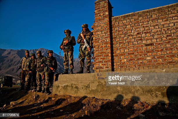 Indian army soldiers look towards the government building where the militants are holed up during a gun battle between militants and Indian...
