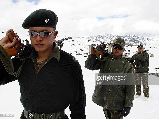 Indian Army soldiers of the Gorkha Regiment carry weapons as they walk through snow along the IndiaChina border at the height of 16000ft near...
