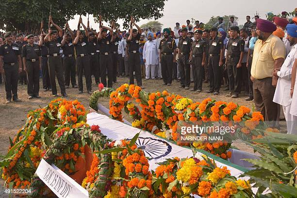 Indian army soldiers perform a gun salute for deceased soldier Gurdev Singh who was killed in an attack by suspected militants in the district...