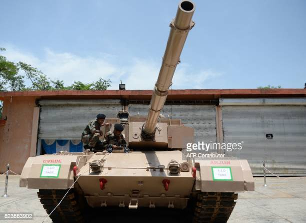Indian Army soldiers sit atop an Arjun tank during a Defence Research and Development organisation exhibition in remembrance of the late Indian...