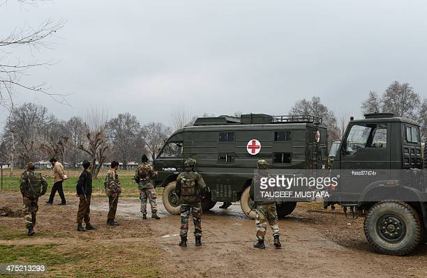 Indian army soldiers stand alongside an ambulance carrying the bodies of soldiers killed inside a army camp at Safapora some 20 kms from Srinagar on...