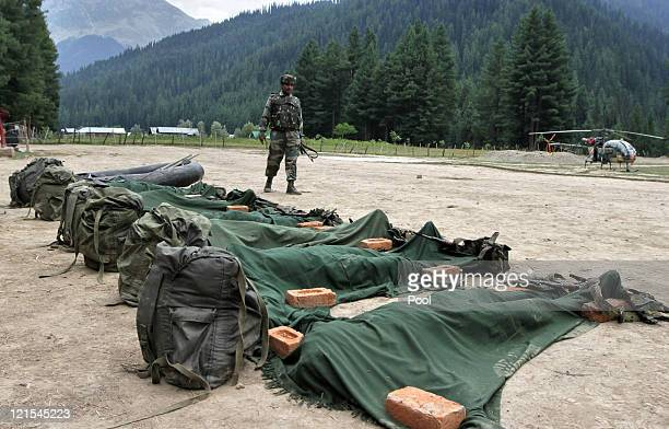 Indian Army soldiers stand guard in front the ammunition and bodies of suspected militants killed by the Indian Army on August 20, 2011 in Gurez,...