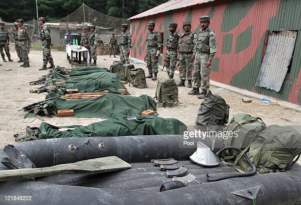Indian Army soldiers stand guard in front the ammunition dinghy and bodies of suspected militants killed by Indian Army on August 20 2011 in Gurez...
