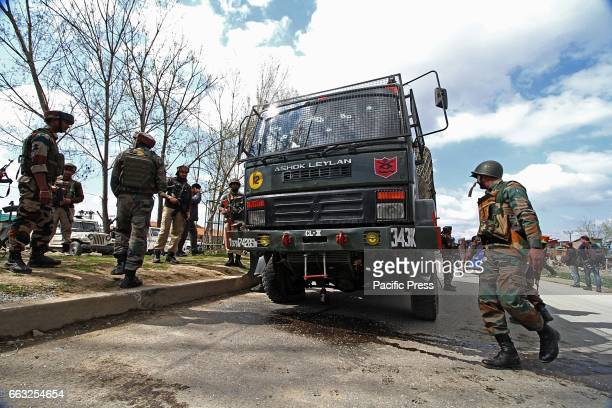Indian army soldiers stand near the damaged vehicle which was attacked by suspected rebels in Bemina Srinagar the summer capital of Indian controlled...