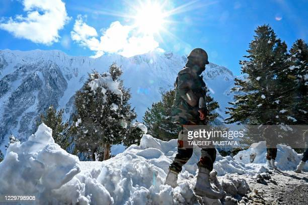 Indian army soldiers stand on a snow covered road after snowfall near Zojila mountain pass that connects Srinagar to the union territory of Ladakh,...