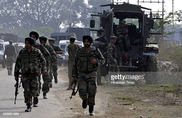 Indian army soldiers take position during a gun battle with armed suspected militants at Pindi Khattar village of the Arnia border sector on November...