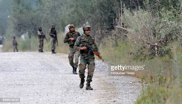 Indian Army soldiers take position near the site of the gunfight at the district police lines in Pulwama about 30km south of Srinagar on August 25...
