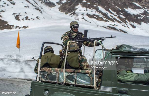 Indian army trooper stands guards at their vehicle at the snowcleared SrinagarLeh highway in Zojila 108 KM far from Srinagar the summer capital of...