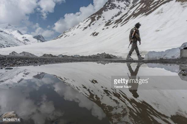 Indian Army trooper walks on the snowcleared SrinagarLeh highway on April 6 2018 in Zojila 108 km east of Srinagar the summer capital of Indian...
