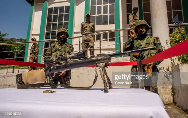 Indian Army troopers stand behind a seized US made sniper rifle recovered by Indian forces at a display during a press conference at Army on August...