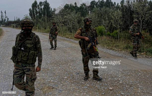 Indian army troopers stand guard on the road leading towards their camp where rebels are fighting with their comrades on August 26 2017 in Pulwama...