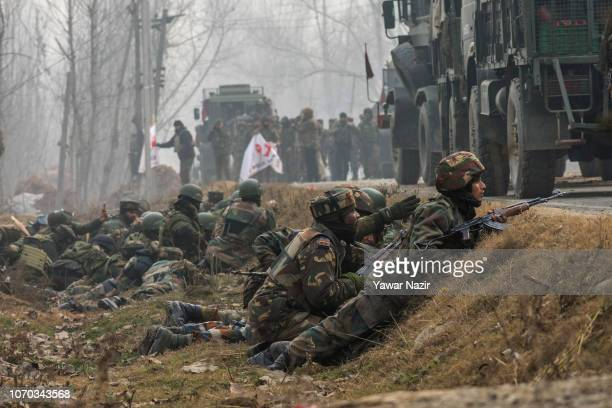 Indian army troopers take position during a gun battle between militants and them on December 9 2018 in the outskirts of Srinagar the summer capital...