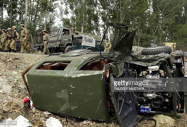 Indian army troops patrol the road near a damaged army vehicle after suspected rebels detonated explosives in a car as an army convoy including a...