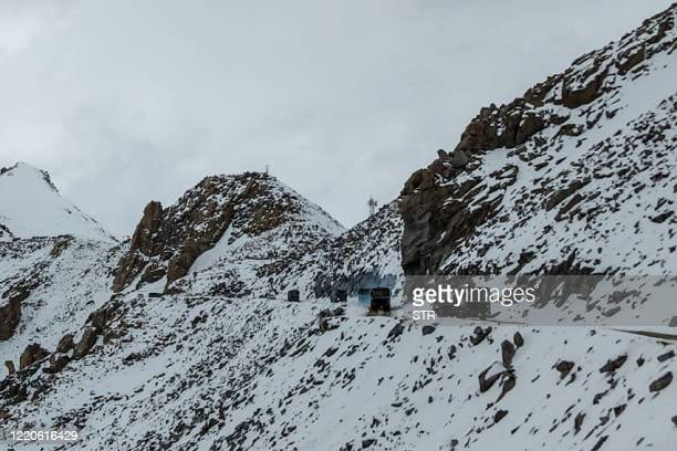 TOPSHOT Indian Army vehicles drive on a road near Chang La high mountain pass in northern India's Ladakh region of Jammu and Kashmir state near the...