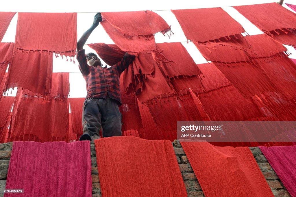 Indian artisan dry stoles after dyeing in Amritsar on November 5 2017 / AFP PHOTO / NARINDER NANU