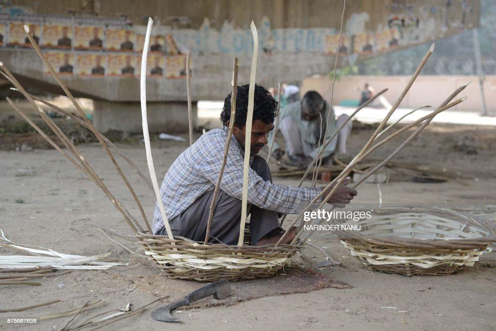 Indian artisan Harbans makes baskets under a bridge in Amritsar on November 18 2017 / AFP PHOTO / NARINDER NANU