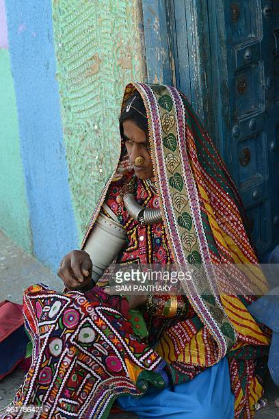 Indian artisan Sona stitches embroidery as she sits at the entrance of a traditional 'Bhunga' or hutshaped residence at Hodka village some 470 kms...