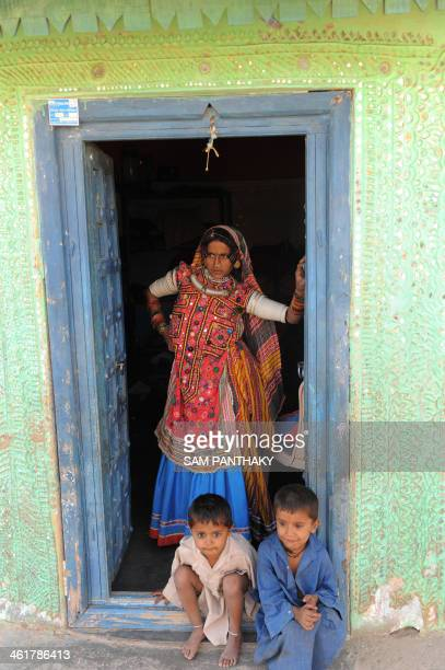 Indian artisan Sona wears traditional embroidered dress as she stands at the entrance of a traditional 'Bhunga' or hutshaped residence at Hodka...