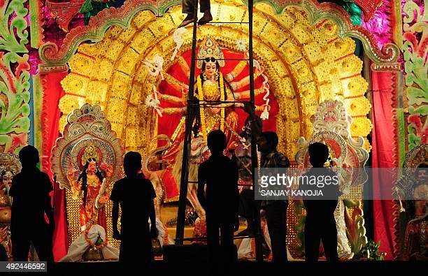 Indian artisans give the final touches to a Durga Puja pandal ahead of the Dussehra festival at Maharishi Mahesh Yogi Ashram in Allahabad on October...