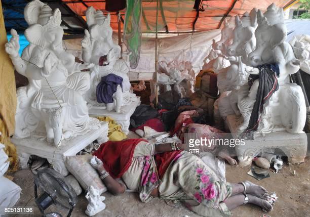 TOPSHOT Indian artisans sleep next to halffinished idols of the Hindu deity Ganesha at a workshop on the outskirts of Jammu on August 1 2017 Idols of...
