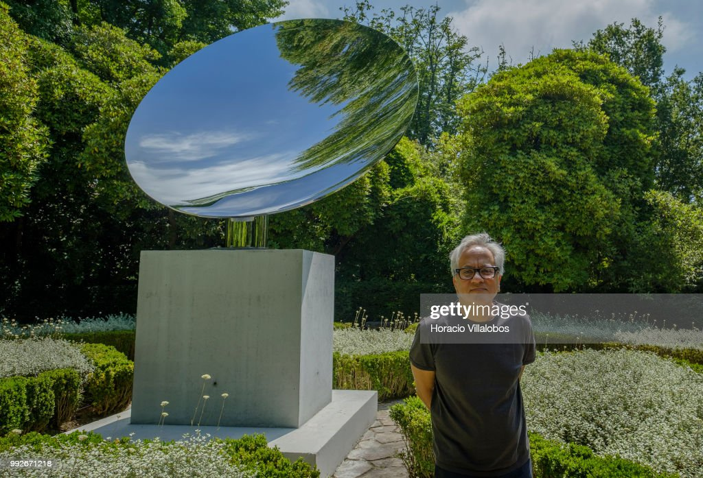 Indian artist Anish Kapoor stands in front of his work Sky Mirror during the presentation to the press of his exhibition 'Anish Kapoor: Works, Thoughts, Experiments' in Serralves Museum and Park on July 06, 2018 in Porto, Portugal. The exhibition presents a selection of outdoor works that are representative of Kapoors sculptural language, its choice and siting of sculptures in the Park of Serralves carefully considered by the artist so as to create an itinerary through time, space, perception and meaning. The central exhibition space of Serralves Museum hosts 56 models of realized and unrealized projects conceived by the artist over the past 40 years showing the intimate scale of the artists studio as a space of thinking and experimentation. 'Anish Kapoor: Works, Thoughts, Experiments' will be opened to the public until January 09, 2019.