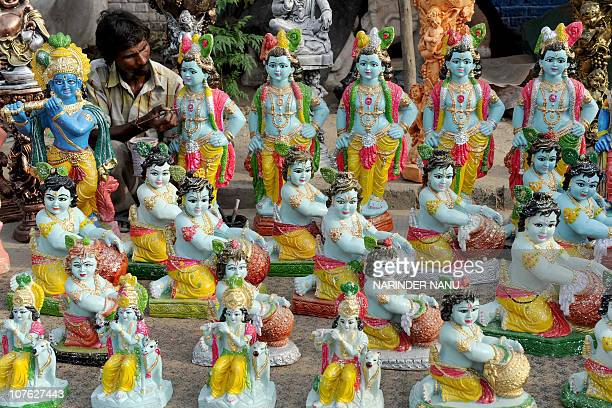 Indian artist Bagha gives the finishing touches to idols of Hindu Lord Krishna at a roadside stall in Amritsar on August 12 2009 The idols are in...