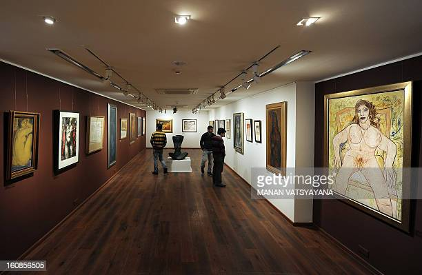 Indian artist FNSouza's painting is displayed as visitors look at an art exhibition The Naked and the Nude in an art gallery in New Delhi on February...