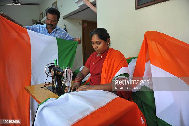 Indian artist Goddeti Rama and husband G Balu prepare a flag for an attempt for the longest Indian national flag record at their home in Hyderabad on...