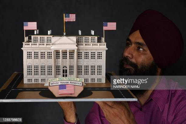 Indian artist Gurpreet Singh displays his paper art work in the form of a model of White House to mark the annual US Independence Day celebrations,...